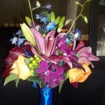 Jewel tones, Lily, Rose, Peony, Calla, Orchid, Delphinium and Hypericum Berry.