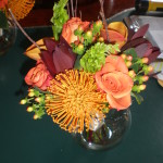 Roses, Mango Callas, Hypericum berries, Belles of Ireland, Safari Sunset and Pincushion protea topped with a few sticks.