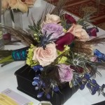 Roses, hydrangea, callas, and delphinium are accented with spiky blue thistle and peacock feathers.