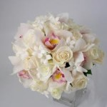 white roses, mini cymbidium orchids and stephanotis blooms complete with pearl insert.