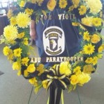 A wreath arrangement with personalized tribute of the deceased time of service.
