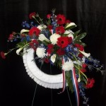 Patriotic red white and blue mix on a white satin wreath.