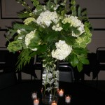 Submerged dendrobium orchids with an elegant white and green arrangement topper finished off with mood setting tealights.
