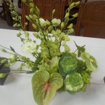 Mixed textures in all green flowers make this centerpiece visually captivating for your guests.