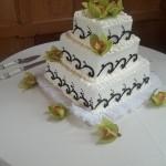 Green cymbidium orchids adorn this simple black and white cake.
