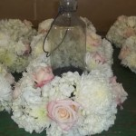 Soft pink and lush white flowers hug this lantern to light up an outdoor evening reception.