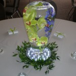 Submerged flowers are naturally magnified by the water so just a few stems can make a visual impact.  Add a uplight disc to make the centerpiece glow for an evening reception.