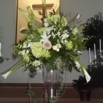 Altar arrangment on tall glass vase.